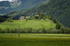 Il paesaggio idilliaco nelle alpi nella primavera con il chalet tradizionale della montagna e la montagna verde fresca pascola co Immagine Stock Libera da Diritti