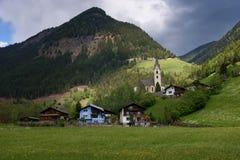 Il paesaggio idilliaco nelle alpi nella primavera con il chalet tradizionale della montagna e la montagna verde fresca pascola co Fotografia Stock Libera da Diritti