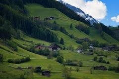 Il paesaggio idilliaco nelle alpi nella primavera con il chalet tradizionale della montagna e la montagna verde fresca pascola co Immagine Stock