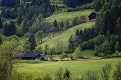 Il paesaggio idilliaco nelle alpi nella primavera con il chalet tradizionale della montagna e la montagna verde fresca pascola co Immagini Stock Libere da Diritti