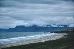 Il paesaggio islandese austero con il campo nella priorità alta e nelle montagne ed i fiordi nei precedenti Immagine Stock