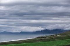 Il paesaggio islandese austero con il campo nella priorità alta e nelle montagne ed i fiordi nei precedenti Fotografia Stock Libera da Diritti