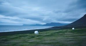 Il paesaggio islandese austero con il campo nella priorità alta e nelle montagne ed i fiordi nei precedenti Fotografie Stock