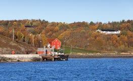 Il paesaggio norvegese, rosso alloggia vicino al pilastro Fotografia Stock Libera da Diritti