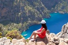 Il paesaggio Oludeniz, Turchia, una ragazza in un vestito rosso esamina il Butterfly Valley da sopra, sedendosi sulle rocce immagini stock