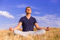 Il paesaggio pacifico di un uomo che medita nella posizione di loto Fotografie Stock Libere da Diritti