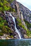Il paesaggio pittoresco: cascata, rocce e mare Fotografie Stock