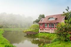 Il paesaggio scenico casa con mattoni a vista dal lago Riflessione in acqua fotografie stock