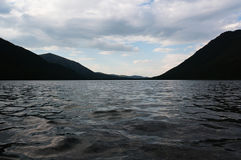Il paesaggio triste con il lago e le alte colline nei precedenti nella sera si accendono Fotografia Stock