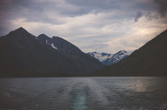 Il paesaggio triste con il lago e le alte colline nei precedenti nella sera si accendono Fotografia Stock Libera da Diritti