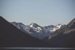 Il paesaggio triste con il lago e le alte colline nei precedenti nella sera si accendono Immagine Stock Libera da Diritti