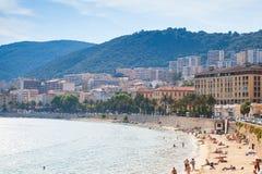 Il paesaggio urbano corso, la gente si rilassa sulla spiaggia Immagine Stock