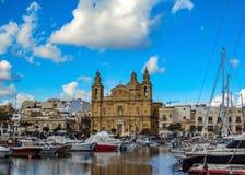 Il paesaggio urbano di La Valletta, la capitale di Malta, con la chiesa e di yahts ha riflesso in acqua, nel giorno soleggiato co fotografie stock libere da diritti