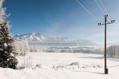 Il paese delle meraviglie austriaco di inverno con le montagne, un palo di potere, una neve fresca e una foschia Fotografie Stock