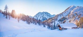 Il paese delle meraviglie di inverno nelle alpi con il chalet della montagna al tramonto Fotografia Stock Libera da Diritti