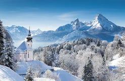 Il paese delle meraviglie di inverno nelle alpi con la chiesa Fotografia Stock