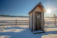 Il paese fuori alloggia con neve e recinta Immagine Stock