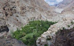 Il paesino di montagna, fra le alte rocce sul fondo della gola è toppa verde degli alberi e delle case agricole bianche vicino al Immagini Stock Libere da Diritti