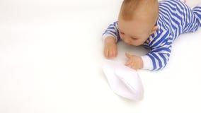Il pagliaccetto a strisce d'uso del bambino sveglio gioca con la barca di carta stock footage
