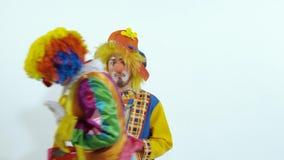 Il pagliaccio di circo che prova a pettinare l'altro è capelli ed infine prendere le grandi forbici stock footage