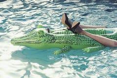 Il paio del ` s delle donne di colore calza a tacco alto fatto da pelle di coccodrillo nella piscina fotografia stock