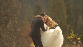 Il paio di nozze in amante sta divertendosi mentre ballava nelle montagne di autunno durante il tramonto Ritratto impressionabile archivi video
