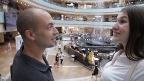 Il paio discende la scala mobile al centro commerciale stock footage