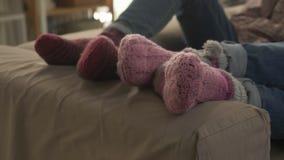 Il paio pallido del ` s delle gambe si trova sullo strato in calzini di lana, vicino al piano, la comodità 60 fps stock footage