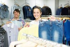 Il paio sceglie i vestiti al deposito Fotografie Stock