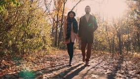 Il paio sposato giovane sta camminando nel parco di autunno, fra gli alberi nudi archivi video
