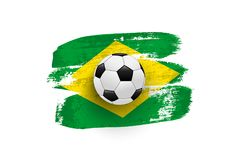 Il pallone da calcio realistico sulla bandiera del Brasile ha fatto dei colpi della spazzola Elemento di disegno di vettore Immagine Stock