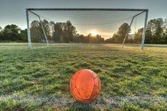 Il pallone da calcio vibrante ha concentrato davanti allo scopo di calcio all'alba Fotografia Stock Libera da Diritti
