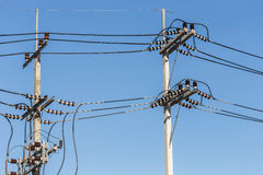 Il palo elettrico collega i cavi elettrici ad alta tensione su cielo blu Immagini Stock