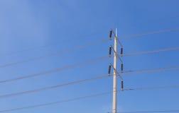 Il palo elettrico di alta tensione con chiaro cielo blu Fotografia Stock
