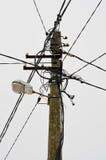 Il palo elettrico si collega ai cavi elettrici ad alta tensione sul fondo del cielo Fotografia Stock