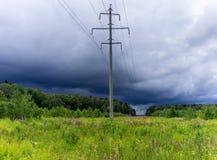 Il palo elettrico sta in un campo verde Sopra il campo della tempesta c Fotografia Stock