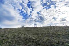Il palo elettrico sulla collina ai precedenti si appanna fotografia stock libera da diritti