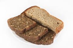 Il pane in bianco e nero su un piatto bianco su un bianco ha isolato il fondo Fotografia Stock