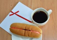 Il pane del hot dog ha riempito l'uva passa crema della fragola ed il caffè nero Fotografie Stock