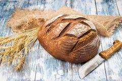 Il pane di segale si trova sulla tela da imballaggio e su un coltello accanto  Immagini Stock