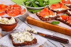 Il pane di segale tosta con formaggio cremoso ed il salmone Fotografia Stock