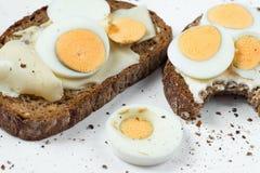 Il pane due con l'uovo sodo affettato, in secondo luogo è morso preso Fotografia Stock Libera da Diritti