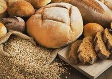 Il pane ed i grani hanno sparso sulla tavola di legno Immagine Stock