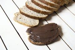 Il pane ed il cioccolato, pane di diffusione del cioccolato, crusca hanno affettato il pane e cioccolato, pane integrale e ciocco Immagine Stock