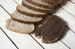 Il pane ed il cioccolato, pane di diffusione del cioccolato, crusca hanno affettato il pane e cioccolato, pane integrale e ciocco Fotografie Stock Libere da Diritti