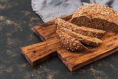 Il pane fresco della segale con i grani ha tagliato su un tagliere Fotografia Stock Libera da Diritti
