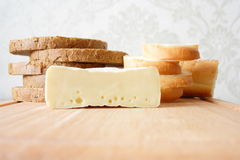 Il pane ha tagliato dai bei pezzi e dal formaggio su una scheda di legno Fotografia Stock Libera da Diritti