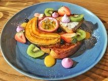Il pane inzuppato in latte/uova e zucchero e fritto in padella con i frutti saporiti è servito sul piatto blu Fotografia Stock