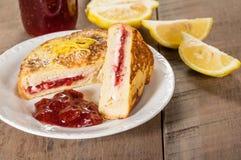 Il pane inzuppato in latte/uova e zucchero e fritto in padella farcito con formaggio cremoso e la fragola si gelatinizzano Immagine Stock