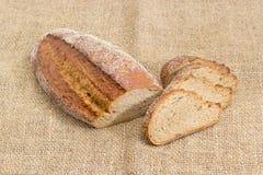 Il pane nero con il tutto ha germogliato i grani del grano su tela di sacco Immagine Stock